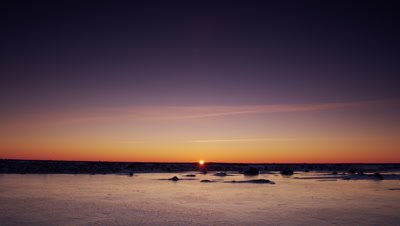Scenic - Sun sets on horizon  over a bare, classy sheet of ice and under a deep blue sky.  Wide.
