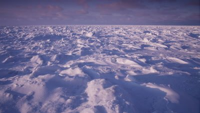 Scenic - Sunset scenic, slow pan across windblown, sculpted snow on vast ice sheet.  Sun at back.  Ext. Wide.