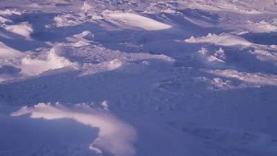 Scenic - Slow tilt up across windblown, sculpted snow that stretches to the horizon. Ext. Wide.
