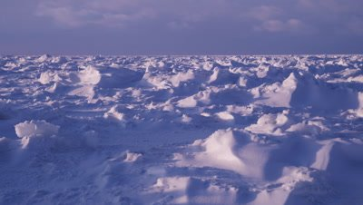 Scenic - Sunset scenic, slow pan across windblown, sculpted snow on vast ice sheet.  Sun at back. Low Angle. Wide.