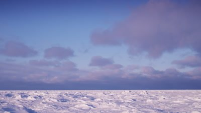 Scenic - Fast moving clouds over vast, wind sculpted ice sheet.  Wide.