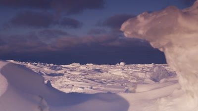 Scenic - Low angle shot with foreground snow formations faming view of wind-sculpted, rugged ice sheet stretching to dark clouds on the horizon.  Wide.  Low Angle.