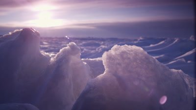 Scenic - Low angle shot of vast ice sheet with focus on foreground snow formations and rugged, sculpted ice stretching behind to the horizon where the sun is setting behind a cloud bank.  Low Angle.  Wide.