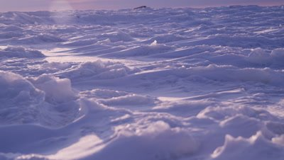 Scenic - Slow pan across foreground ice sheet that has been shaped and sculpted by winds.  Focus starts on distant ice then racks in to focus on foreground, pan stops to reveal intricate snow shapes.  Rugged ice stretching to the horizon in background.  Low Angle.  Wide.
