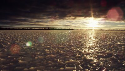 Dollying wide scenic.  Camera drifts across bizarrely shaped ice surface at sunset as sun beams out from beneath a heavy cloud layer.  Boreal forest visible on the horizon.  Wide.