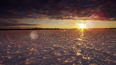 Dollying wide scenic.  Camera drifts across bizarrely shaped ice surface at sunset as sun beams out from beneath a heavy cloud layer.  Boreal forest visible on the horizon.  Camera drifts towards horizon.  Wide.