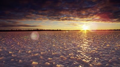 Dollying wide scenic.  Camera drifts across bizarrely shaped ice surface at sunset as sun beams out from beneath a heavy cloud layer.  Boreal forest visible on the horizon.  Camera drifts away from horizon.  Wide.