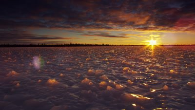 Wide scenic.  Bizarrely shaped ice surface in foreground  at sunset as sun beams out from beneath a heavy cloud layer.  Boreal forest visible on the horizon.   Wide.