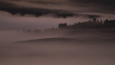 Sunrise timelapse.  Detail shot of mist rolling over trees and ridges as the sun starts to rise.  Med.