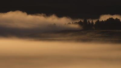 Sunrise timelapse.  Detail shot of mist rolling over trees and ridges as the sun is rising, casting golden light across the valley and mist.  Med.