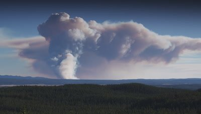 Timelapase of smoke rising and spreading out form a forest fire burning in a forest on the horizon.  Wide.