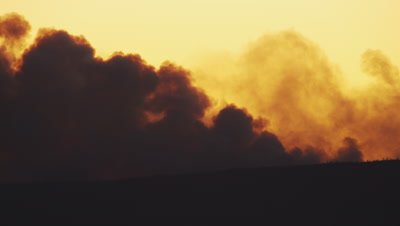 Scenic timelapse.  Heavy smoke roils up form a forest fire over Yellowstone Lake at sunset.  The smoke is a mix of dark grey and angry red.  Med.
