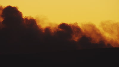 Heavy smoke roils up form a forest fire over Yellowstone Lake at sunset.  The smoke is a mix of dark grey and angry red.  Med.