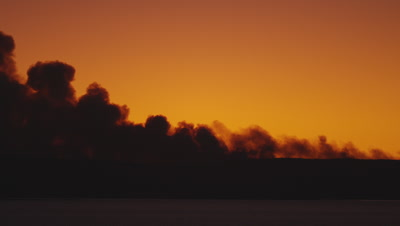Heavy smoke roils up form a forest fire over Yellowstone Lake at sunset.  Pan along the shore of the lake, following the billowing smoke.  The smoke is a mix of dark grey and angry red.  Med.