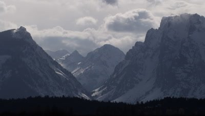 Scenic time lapse of clouds billowing and forming on the snowy, jagged flanks of the Grand Tetons.  Med.