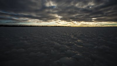 Low-angle shot of the sun setting over  a frozen boreal forest pond.  Ice on pond is frozen into bizarre knobs and shapes.  The sun slips beneath a textured and contrasty cloud layer to light up the ice surface with golden light.  Wide.