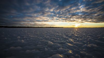 Low-angle shot of the sun setting over  a frozen boreal forest pond.  Ice on pond is frozen into bizarre knobs and shapes.  The sun slips beneath a textured and contrasty cloud layer to light up the ice surface with golden light.  Shot goes to almost black as the sun disappears below the horizon.  Wide.