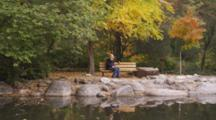 Fair Haired Pregnant Woman, Sits On Bench At Duck Pond