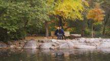 Fair Haired Pregnant Woman, Sits On Bench At Duck Pond, Joined By Husband