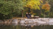 Fair Haired Couple, Pregnant Woman, Sit On Bench At Duck Pond, He Rests His Head On Her Belly