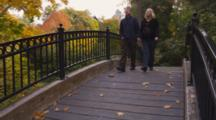 Fair Haired Couple, Pregnant Woman, Cross Bridge In Park With Fall Colors