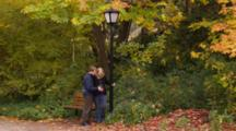 Fair Haired Couple, Pregnant Woman, By Old Street Lamp In Park, Man Rubs Woman's Belly