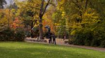 Fair Haired Couple, Pregnant Woman, Walk On Path Near Playground