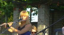 Woman In Band Plays Flute At Outdoor Party