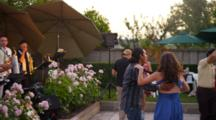Musicians In Band Play For Outdoor Party While People Dance
