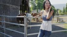 Woman Talks On Phone Near Livestock Corral