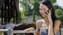 Woman Talks On Phone Near Livestock Corral