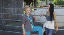 Women Stand Talking Near Livestock Corral