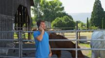 Man Talks On Phone Near Livestock Corral