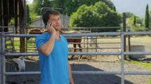 Man Talks On Phone Near Livestock Corral