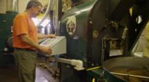 Man Adjusting Coffee Roaster Machinery, Roasted Coffee Beans Being Stirred In Vat