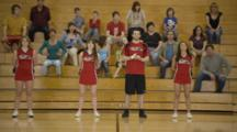Cheerleaders Cheer On Basketball Court, One Girl Fails To Tumble, Fans Behind