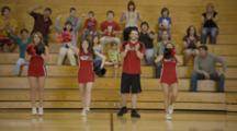 Cheerleaders Cheer On Basketball Court, One Girl Tumbles, Fans Behind