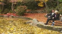 Couple Sits On Park Bench Near Duck Pond, Fall Colors