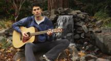 Young Man Playing Guitar, Singing, By Waterfall In Park