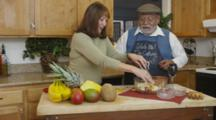 Private Home, Retired Couple Preparing Fruit Salad In Kitchen, Cooking Together