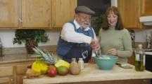 Private Home, Retired Couple Feeding Each Other Pasta In Kitchen, Cooking Together