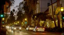 Cars And Pedestrians On State Street In Santa Barbara In Evening, Lights On Trees, Shop Windows