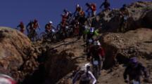 A Large Group Of Mountain Bikers Race Over A Rocky Trail.