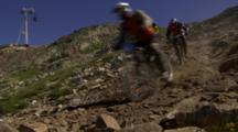 Mountain Bikers Race Down A Rocky Trail.
