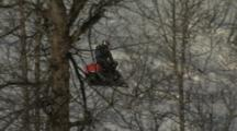 Zoom Out Of A Snowmobiler Riding Away Into A Mountain Gully.