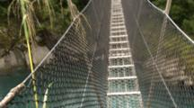 A Point Of View Shot Of A Rope Bridge Over A River In Forest