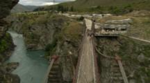 Zoom Out And Pan From A Blue River To A Bridge With Tourists On It.