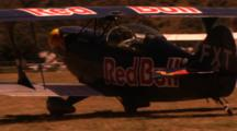 Close Up Of A Red Bull Stunt Plane Driving On A Field.