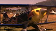 Red Bull Stunt Plane Drives Across A Field.