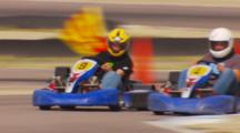 Zoom Out From Go Karts Racing To A Man Waving A Checkered Flag.